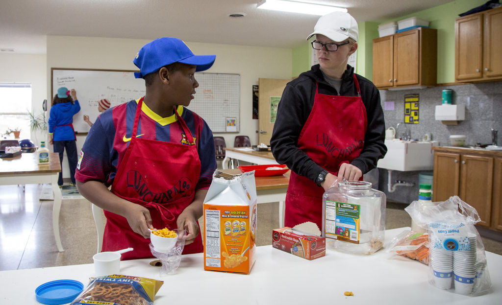 Xavier Smith, left, 12, 7th grade, and Christopher Queoff, 13, 8th grade, fill orders in a lunch program the students run at Madison Community Montessori School.