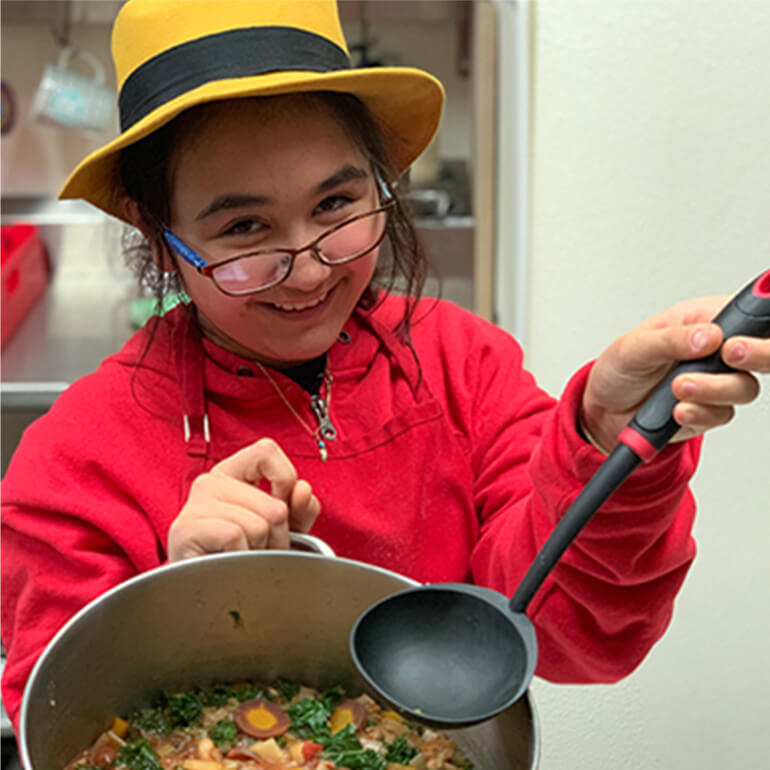 An adolescent holding a ladle and a pot of stew