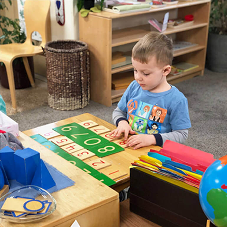 A young child playing with a learning numbers toy in a classroom