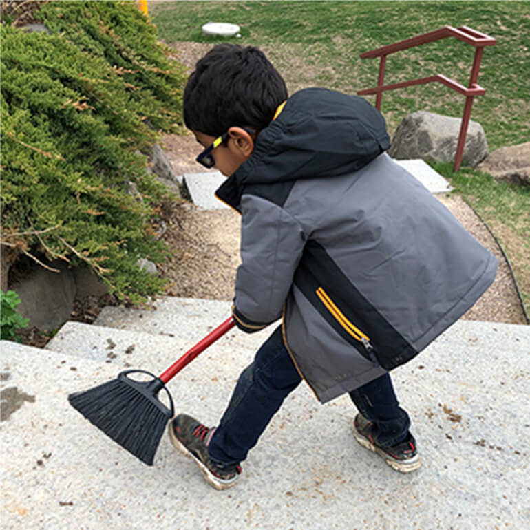 A child sweeping a set of concrete stairs ourdoors
