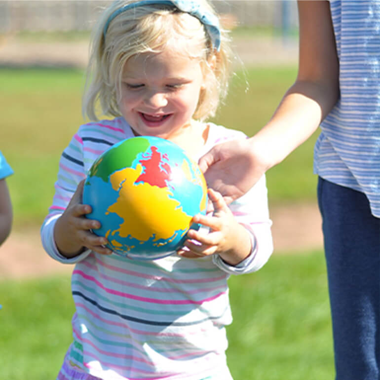 Toddler holding a globe outside